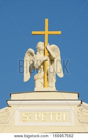Sculpture of an angel with a cross on the roof of the Lutheran Church.