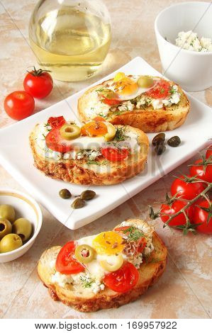 Bruschetta crostini with cream cheese with cherry tomatoes herbs olives capers and fried egg