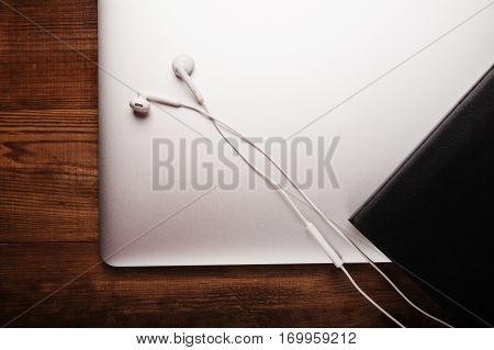 Notebook, headphone and diary on the wooden table. Business.