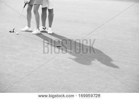 Low section of couple playing golf at course
