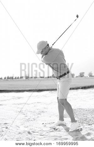 Middle-aged man swinging at golf course against clear sky