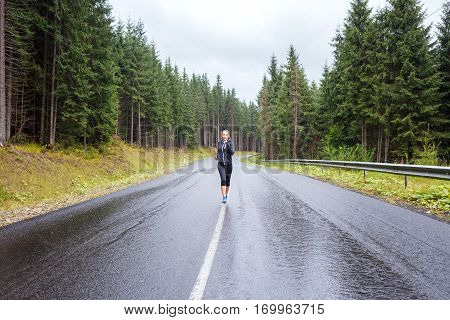 Young athletic woman jogging on rainy hillside road