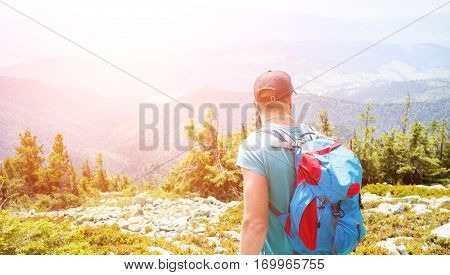 Young man with backpack hiking in the mountains. Summer backpacking background.