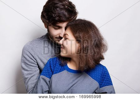 People love and relations. A sylish couple standing over white background. Fashionable bearded man wearing grey sweater hugging his beautiful girl. A lovely couple having rest being happy