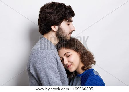 Young couple in love. A pretty young girl snuggling up to her bearded boyfriend. Sincere love between hipsters. Couple supporting each other and relying on each other having nice time together