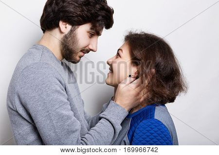 Relations and feelings. Bearded hipster touching gently his girfriend`s face. A happy couple looking at each other`s eyes with great love. Eye contact of lovers. Young pair spending their free time