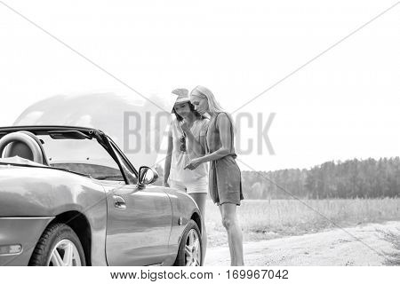 Women examining broken down car on sunny day against clear sky