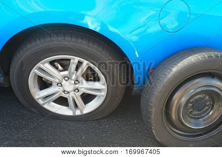 Flat tire on car, replacing with spare dummy