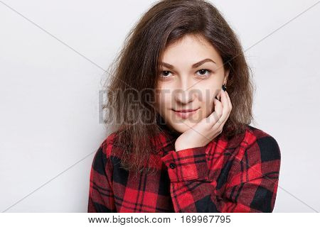 Beautiful young brunette woman in a red checked shirt holding her hand on chin looking confident into the camera isolated over white background. A confident expression of pretty girl