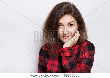 A photo of young very beautiful brunette girl with dark eyes in a red checked shirt looking happily into camera holding her hand on chin standing over white background. People and lifestyle concept