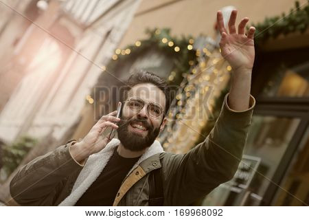 Guy with a beard asking for a taxi while on the phone