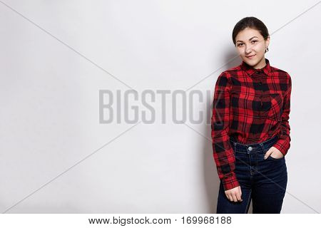 A young sylish hipster girl wearing red checked shirt and jeans holding her hand in the pocket having happy expression standing near white wall. People style and fashion concept.