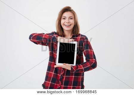 Portrait of a smiling casual woman showing blank tablet computer screen isolated on a white background