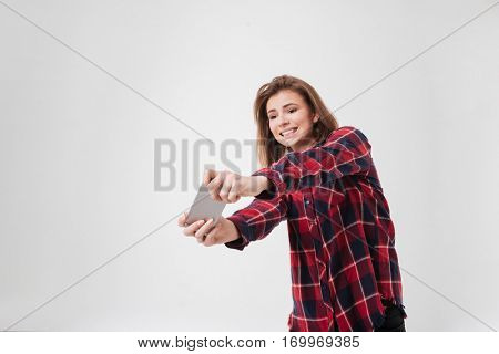 Portrait of a cute young girl in plaid shirt playing on mobile phone over white background