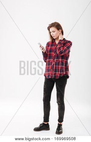 Full length portrait of a casual young woman in plaid shirt standing and using mobile phone over white background