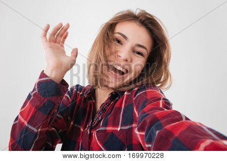 Portrait of a happy laughing woman making selfie photo on smartphone isolated on a white background