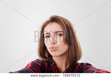 Funny young woman taking selfie and grimacing isolated on a white background