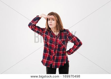 Thoughtful young woman in plaid shirt with hand at her forehead looking far away over white background