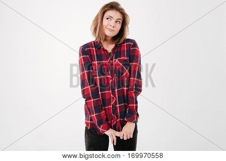 Charming shy woman in plaid shirt standing and looking away over white background