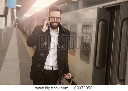 Brown-haired guy about to get on the train with his luggage while on the train
