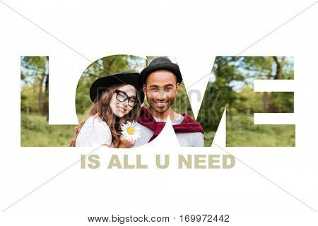 Close up portrait of a young smiling multiracial couple in love looking at camera outdoors, all you need is love signature