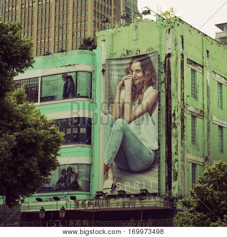 Macao - October 2016: Street view with fashion billboard on old building.