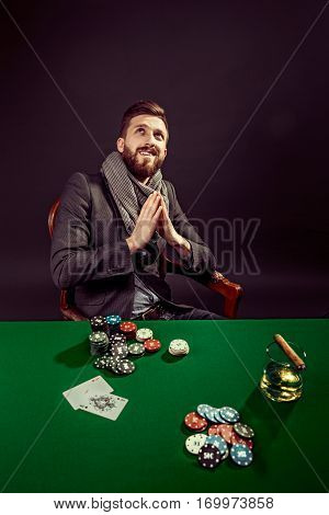 Portrait of smiling bearded elegant man at poker table blessing god looking up