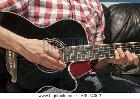 Playing chords on a black acoustic guitar