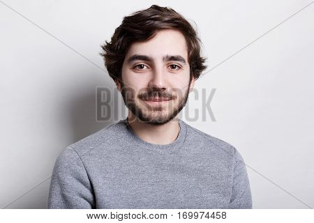 Studio portrait of fashionable bearded man wearing grey casual sweater looking pleased into the camera posing against white wall. Emotions and feelings. Young hipster with beard and fair skin