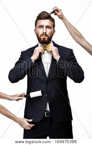 Bearded man in dark suit. sticky brush for cleaning clothes from dust. Gold bowtie. Hair Style.