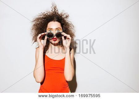 Surprised Unusual model peeping out from under the sunglasses and looking at camera. Isolated gray background