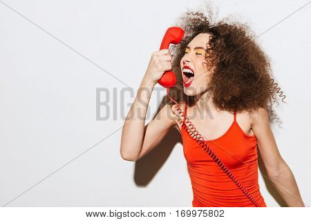 Unusual model screaming at handset with closed eyes. Isolated gray background