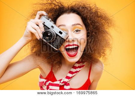 Happy Bright model with open mouth making photo on retro camera. Isolated orange background