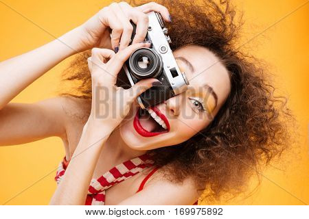 Crazy Bright model with open mouth making photo on retro camera. Isolated orange background