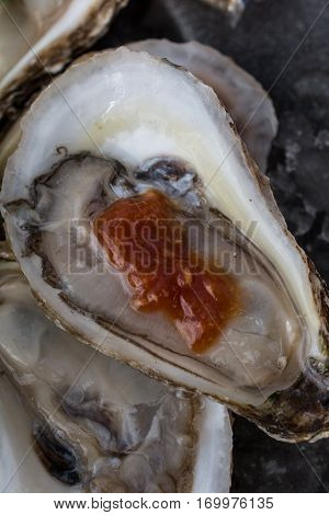 A close up of cocktail sauce on a Raspberry Point Oyster from Prince Edward Island, Canada