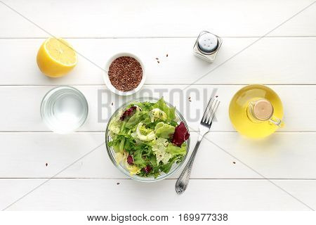 Bowl of fresh salad with flax seed oil and lemon on wooden table. Top view.