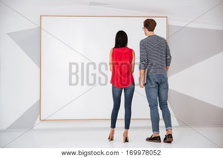 Back view of young couple on exhibition looking at empty blank board. Full length image