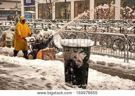 City worker is blowing snow from storm Niko off the street for pedestrian on February 9th, 2017.