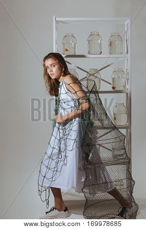 Full length of pretty young woman walking and holding fishing net