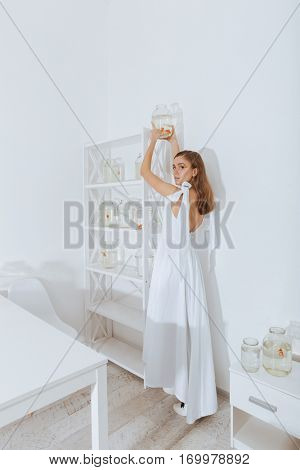 Beautiful young woman standing and putting jar with gold fish on the shelf in the room