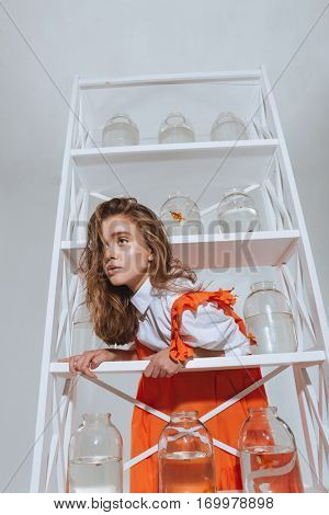 Beautiful young woman standing and looking through the closet with gold fishes in jars