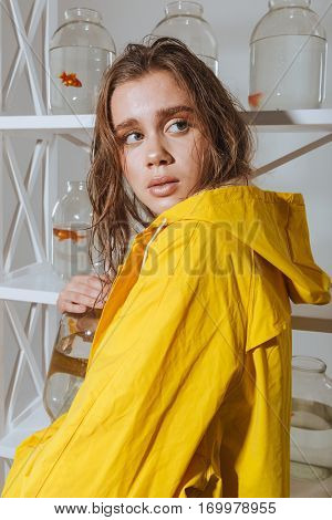 Scared young woman in yellow raincoat standing and hiding jar with gold fish