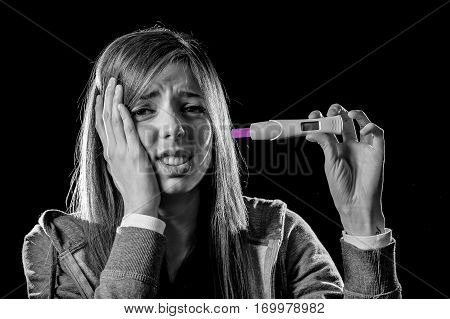 young sad pregnant woman or female teenager scared and shocked holding pregnancy test positive result looking unhappy and in depression isolated in unexpected and irresponsible motherhood
