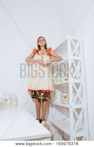 Charming young woman with gold fish in jar standing on the chair in the room