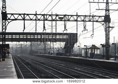 silhouetted footbridge and pylons over a train station in the suburbs