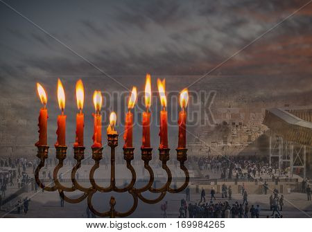 Composite image of menorah with glittering candles and western wall in Jerusalem. The image symbolizes Hanukkah Holiday and Jewish desires and hopes. Low key image toned for retro style