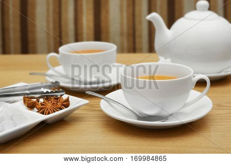 Two cups of tea, tongs and plate with sugar and spices on wooden table