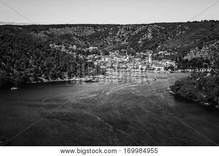 Town Of Skradin On Krka River In Dalmatia, Croatia Viewed From Distance. Black And White Image.
