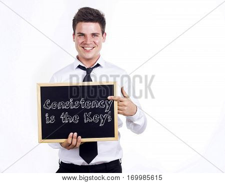 Consistency Is The Key! - Young Smiling Businessman Holding Chalkboard With Text