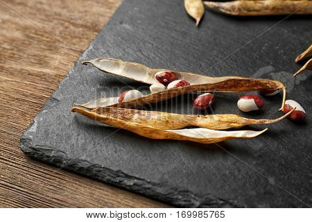 Closeup of haricot bean pods on slate plate